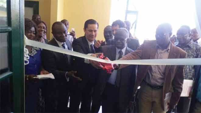 Dr Victor Agyemang (4th left ), the Director-General of the CSIR, being assisted by Mr Daniel Lauchenauer (3rd left) to cut the tape to inaugurate the refurbished laboratory